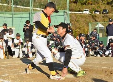 仁志氏(中央右)から打撃時の体の使い方を教わる球児=24日、八頭町徳丸の八頭総合運動公園野球場