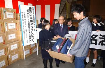 鉛筆や通学用バッグが詰められた荷物を見送る高校生1万人署名実行委メンバー=長崎市、三協