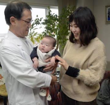 和葉ちゃんを抱く差波医師(左)に感謝の言葉を述べる石岡さん=24日、八戸市