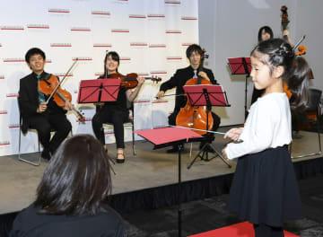 「カーネギーホール・ノータブルズジャパン」のイベントで、指揮者体験をする女の子=25日午後、東京都内