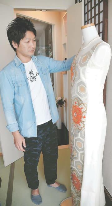 律子さんが縫ったウエディングドレスを眺める卓也さん