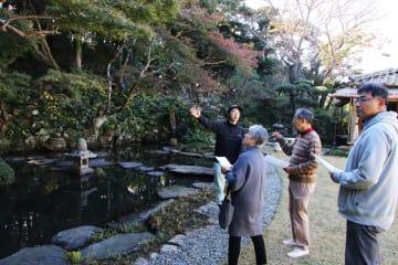 南九州大のOB(左)の説明に耳を傾ける見学者ら=平戸市、棲霞園