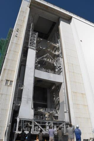 大型ロケット組み立て棟の巨大な一枚扉が開く様子を眺める人たち=南種子町の種子島宇宙センター