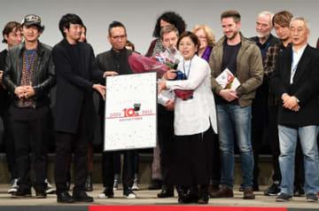 閉幕式で10回記念のパネルを贈られた部谷代表(最前列右)
