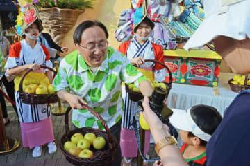 来場者に青森県産リンゴを手渡す三村知事(左2)=23日、海洋公園(NNA撮影)