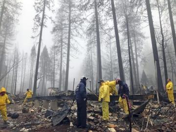 米カリフォルニア州の山火事現場で、捜索活動をするボランティア=23日(AP=共同)