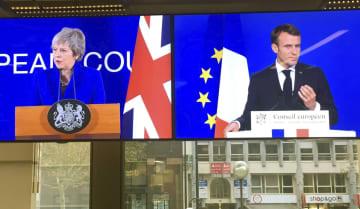 25日、EU本部でのメイ英首相(左)とフランスのマクロン大統領の記者会見を生中継する、同本部内のカフェに掲げられたモニター画面=ブリュッセル(共同)