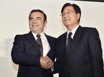 2016年5月12日、資本業務提携の発表記者会見で握手を交わす日産自動車のカルロス・ゴーン社長(左)と三菱自動車の益子修会長=横浜市(肩書は当時)