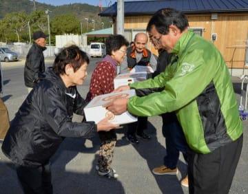 仮設住宅の住民(左)に復興みかんを手渡す関係者