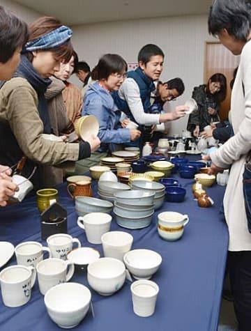 陶器を品定めする来場者=25日、鳥取市富安2丁目の日本海新聞ビル5階ホール