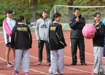 女子選手を指導する大村監督(右から2人目)と広沢選手(左から3人目)=県立総合運動公園補助競技場