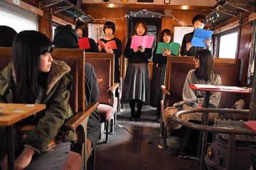 ストーブ列車の客車内で歌声を響かせた弘前大学アカペラサークルのメンバー