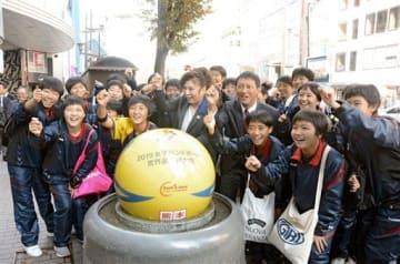 ハンドボール模様にラッピングされたグラニットボールと記念撮影をする八代亜紀さん(中央)や宇土鶴城中のハンドボール部員ら=熊本市中央区