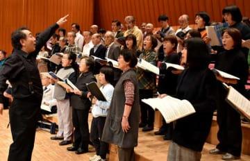 指揮者の山下さん(左)から情熱的な指導を受けるのべおか「第九」を歌う会のメンバー