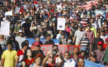 メキシコ北西部ティフアナで、米国境に向かって歩く移民ら=25日(ロイター=共同)