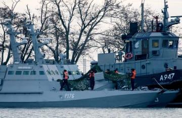 ロシアが実効支配するウクライナ南部クリミア半島東部のケルチ港にえい航されたウクライナ海軍の艦船(手前)とタグボート=26日(タス=共同)