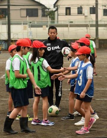 児童にサッカーを教えるSC相模原の冨田さん(中央)=相模原市立上溝小学校