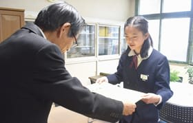 武田教育長から表彰状を受け取る坂下さん(右)