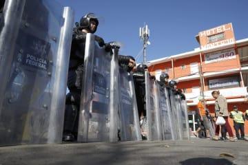 メキシコ北西部ティフアナで、移民収容施設付近を警戒する警察官ら=26日(共同)