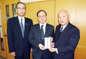 山中会長(右)に義援金を手渡す山下代表(右から2人目)と藤井副代表