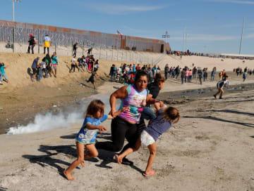 メキシコ・ティフアナの米国境地帯で、催涙ガスの煙から逃れようと双子の娘の手を引いて走る女性=25日(ロイター=共同)