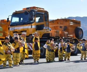除雪車の前で虎舞を披露し、作業員を激励する平田こども園の園児たち