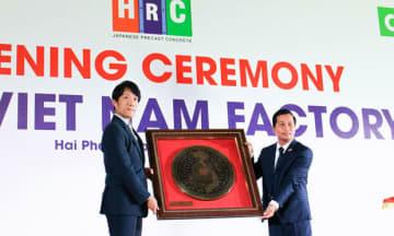 記念品を交換するヒノキヤグループの近藤社長(左)とCJSCのグエン・フー・ティン社長=27日、ハイフォン市