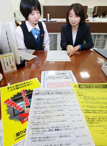 現金払い戻し時に顧客に求めるアンケート項目を見直す広島銀行の行員