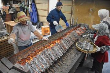 うちわであおぎながら、手際よくイワシを焼き上げる浜小屋の人たち=27日午後、むつ市脇野沢九艘泊