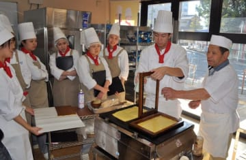 【生徒にあん巻きの作り方を手ほどきする長井さん(右端)=津市大谷町の三重調理専門学校で】