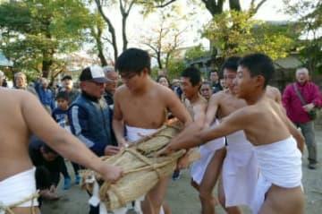 かまぎの中の餅を奪い合う若衆と、投げられる餅を待つ見物客=中津市中殿の貴船神社