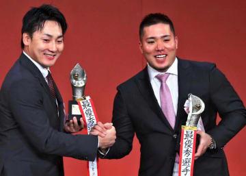 MVPを受賞し、笑顔で握手を交わす広島・丸(左)と西武・山川=東京都内のホテル