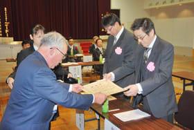 熊谷会長(左)から表彰状を受け取る永年勤続者