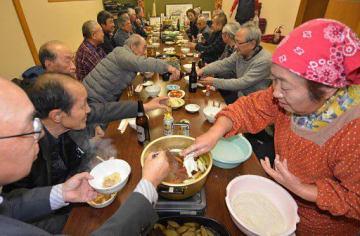 会員の女性(右)が鍋に入れるひっつみを味わい、親睦を深めた集い