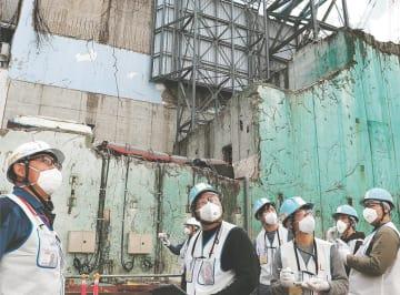 爆発の傷痕が今なお痛々しい3号機を背に、福島第1原発を視察する次世代塾修了生ら