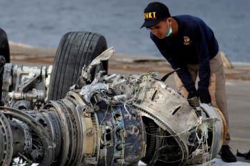墜落したライオンエア機のエンジン部分を調べるインドネシア国家運輸安全委員会の職員=4日、ジャカルタ(ロイター=共同)