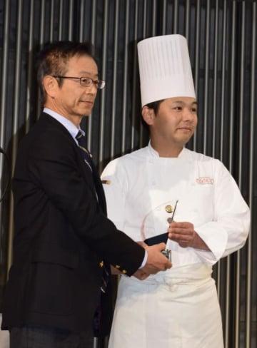 表彰式で盾を受け取る永尾彰英さん(右)=28日午後、松山市湊町5丁目