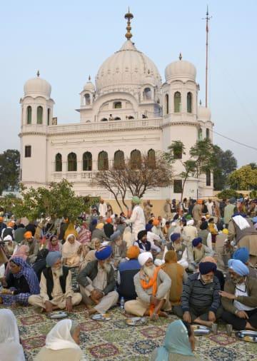 28日、パキスタン中部ナロワルの寺院を訪れるシーク教徒ら(共同)