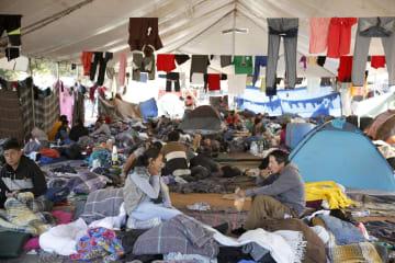収容施設に張られた大型テントの中でくつろぐ移民ら=28日、メキシコ北西部ティフアナ(共同)