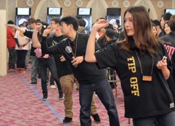 真剣な表情でダーツの腕前を競う参加者たち