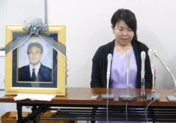 園田耕治さんの遺影を横に、記者会見する妻の真弓さん=29日午後、福岡地裁