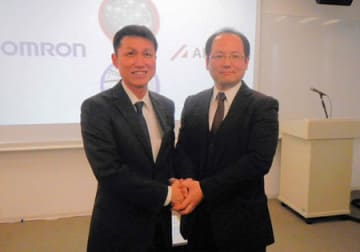 提携を発表し握手するオムロンの福井技術開発本部長(左)とエイシングの出澤社長=京都市下京区