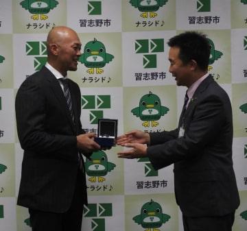 宮本市長(右)から記念品を受け取り笑顔を見せる福浦選手=29日、習志野市役所
