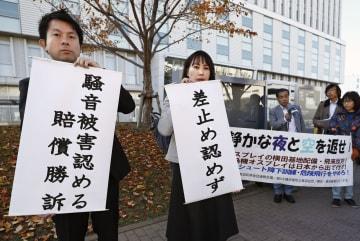 第9次横田基地公害訴訟の判決で、東京地裁立川支部前で垂れ幕を掲げる原告側弁護士=30日午前、東京都立川市