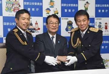 写真撮影に応じる(左から)松本利夫さん、山本国家公安委員長、杉良太郎さん=30日午後、東京・霞が関