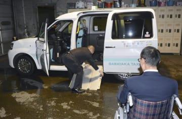 練習で乗降用スロープを設置する菊池孝博さん(奥)ら=11月、札幌市