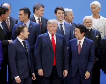 G20首脳会合の会場で、記念写真の撮影を待つ(前列左から)フランスのマクロン大統領、トランプ米大統領、安倍首相=30日、ブエノスアイレス(ロイター=共同)