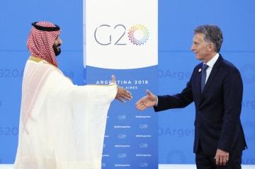 G20首脳会合を前に、アルゼンチンのマクリ大統領(右)の出迎えを受けるサウジアラビアのムハンマド皇太子=30日、ブエノスアイレス(共同)