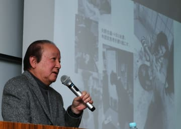 写真でカネミ油症の悲惨さを振り返る写真家の河野さん=長崎市、長崎大
