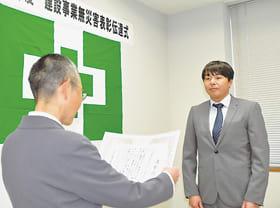 山﨑署長から表彰状を受け取る中陳作業所長(右)